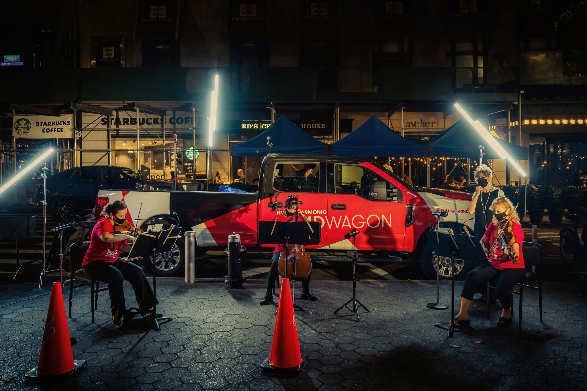 "Three members of the New York Philharmonic perform in front of the orchestra's red pickup truck ""Bandwagon,"" as part of the ensemble's new pop-up series."