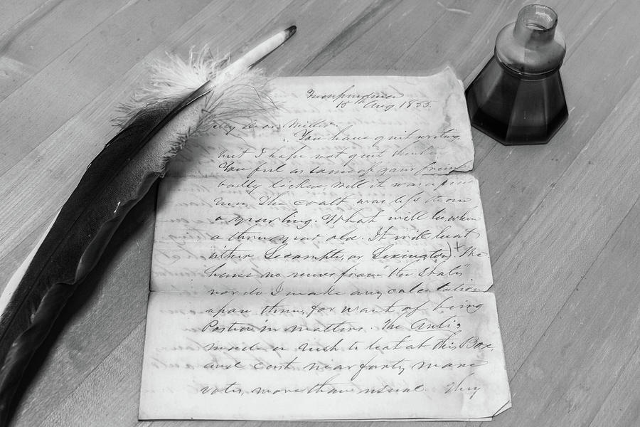 Black and white handwritten letter on aged paper with quill and inkpot