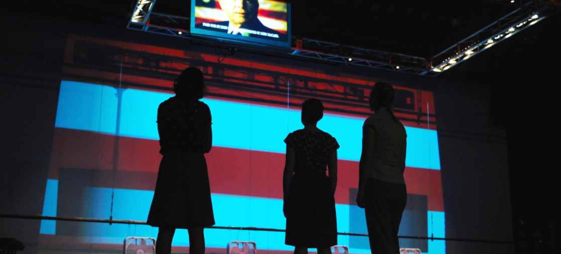 Silhouette of three students against the backdrop of the American flag, looking up at a screen of election coverage in the 2008 production of The Race at Georgetown University.