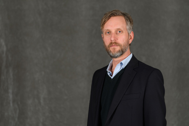 Georgetown University Music Program Professor Ben Harbert wears a black suit and blue shirt, posing against a gray background.