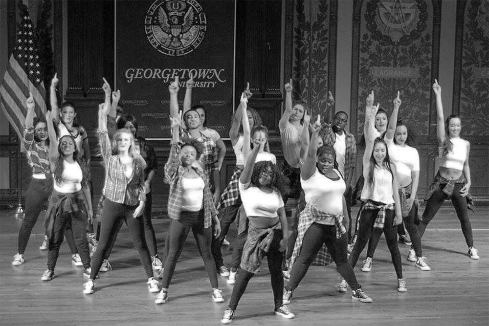 Georgetown student dancers from the hip-hop ensemble Groove Theory strike a pose on the Gaston Hall stage.