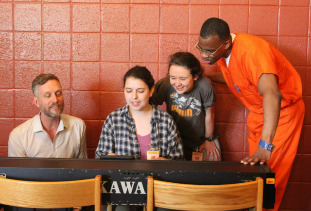Two students, a professor, and an inmate gather around a piano at the D.C. Jail.