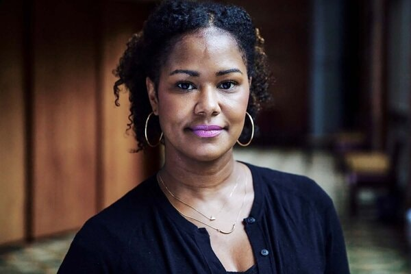Georgetown University Prof. Soyica Diggs Colbert in a black shirt and hoop earrings, sits in the lobby of the Davis Performing Arts Center.