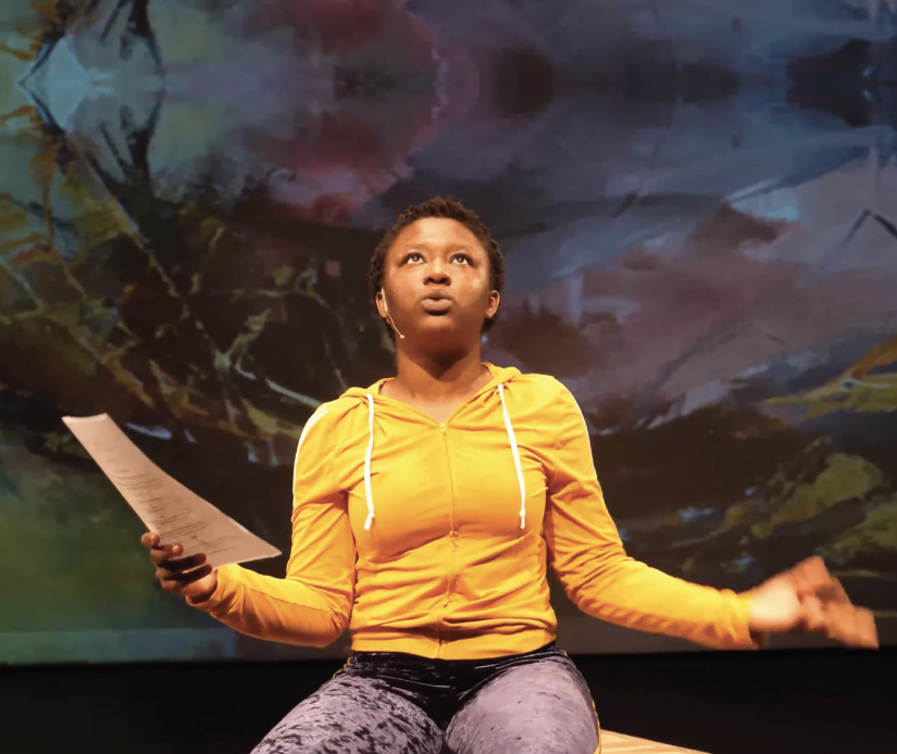 """Fatima Dyfan (C'21) kneels, looking up with arms outstretched, in her senior thesis performance of """"Sunbath,"""" part of the GU Theater & Performance Studies Program's 2020-21 season."""