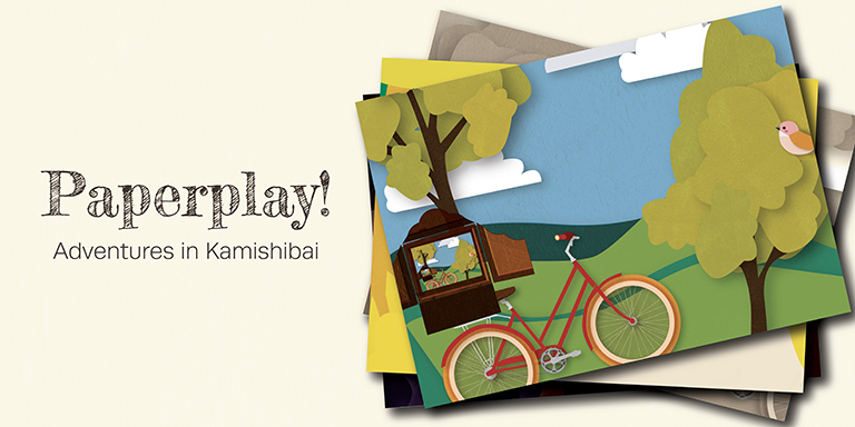 Paper placards fanned out in a stacked pile show the top image of a bicycle with attached butai, half picture frame, half theater stage, against a backdrop of grass and trees.